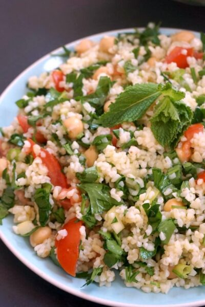 A light blue plate with chickpea tabbouleh