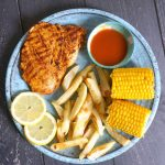 Overhead shoot of a blue plate with butterfly chicken breast, 2 slices of lemon, fries, 2 corns on the cob and a small bowl of chilli sauces