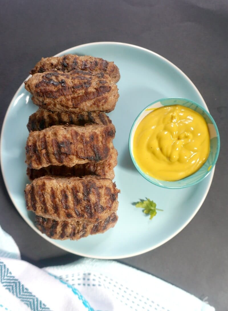 Overhead shoot of a blue plate with Romanian mici and a small bowl of yellow mustard
