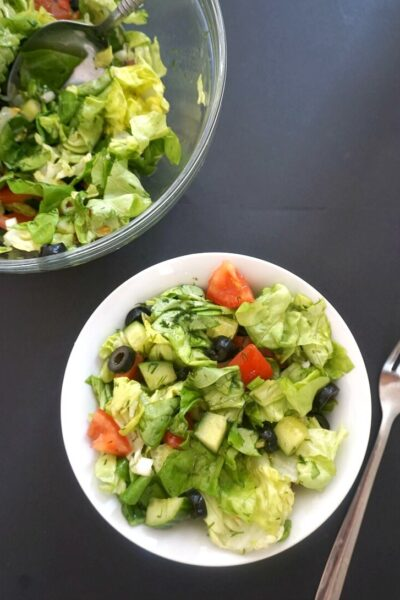 Overhead shoot of a white bowl of green salad and a large bowl of salad