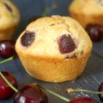 3 cherry muffins with cherries around them