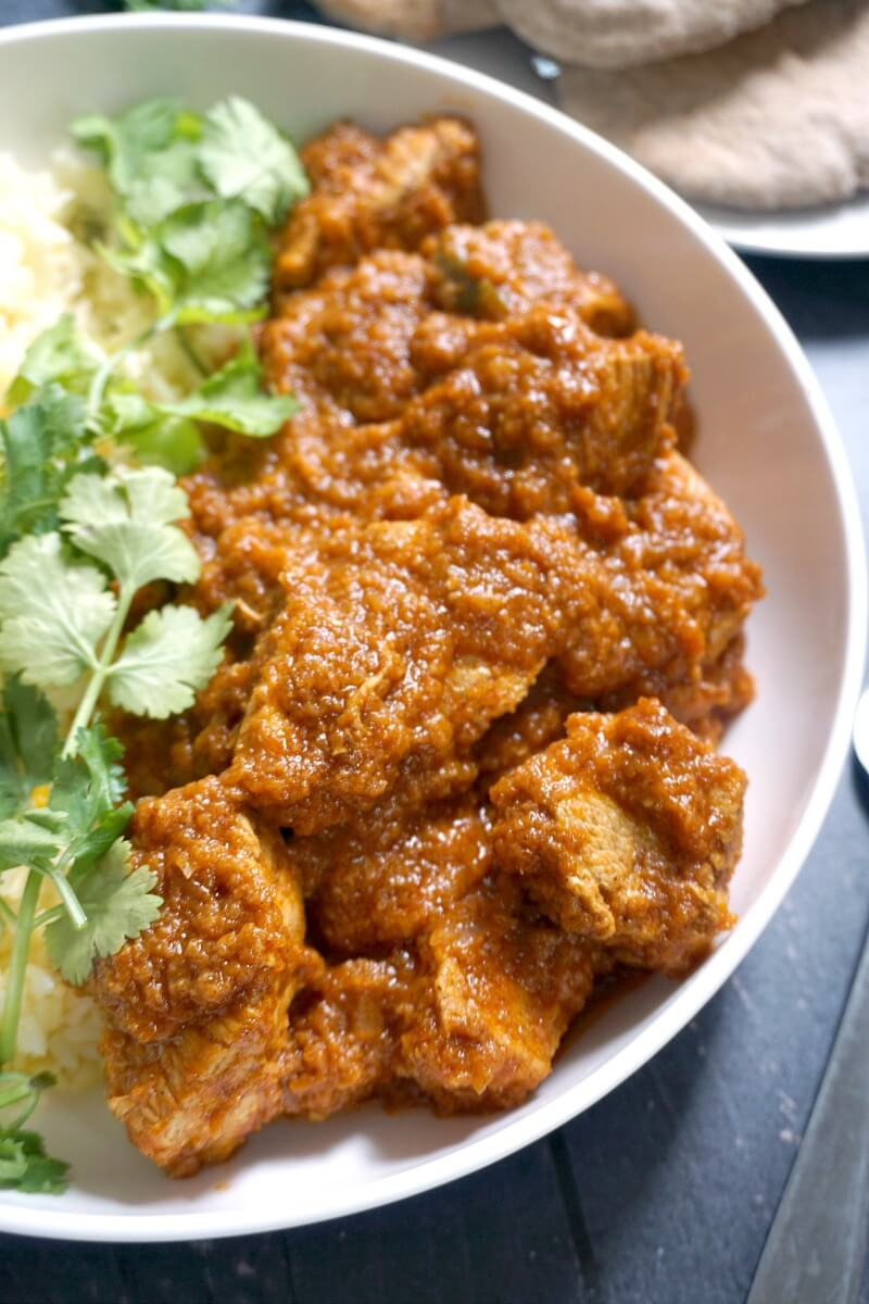 Close-up shoot of a white plate with chicken rogan josh curry