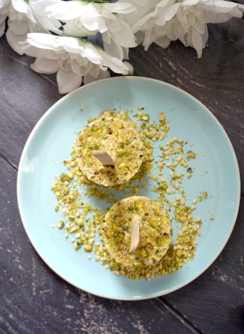 Overhead shoot of 2 kulfi ice creams on a blue plate garnished with chopped pistachios