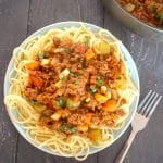 Overehead shoot of a plate with spaghetti and quorn bolognese and a fork next to the plate
