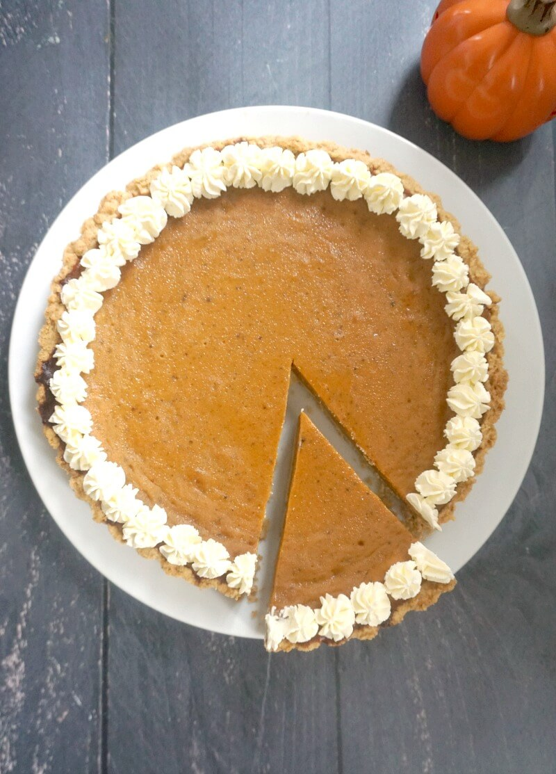 Overhead shoot of a pupkin pie on a white plate with a slice cut out