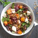 Overhead shoot of a white bowl of pumpkin and quinoa salad
