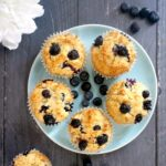 Overhead shoot of a blue plate with 5 vegan blueberry muffins and fresh blueberries scattered around