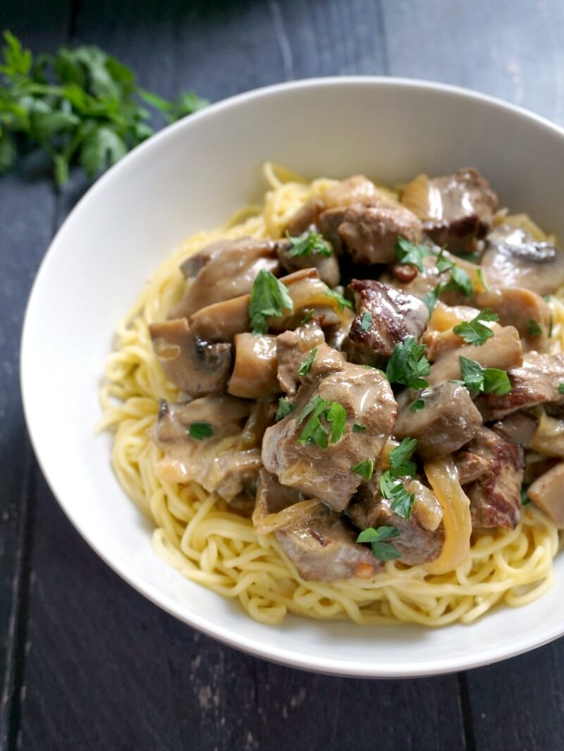 A white plate with noodles and beef stroganoff cooked in the slow cooker