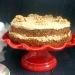 A red cake stand with a coffee and walnut cake