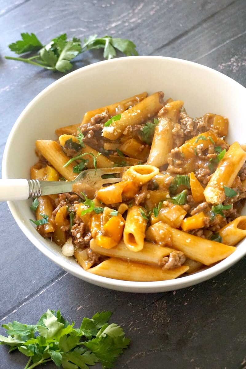 A white bowl with ground beef pasta