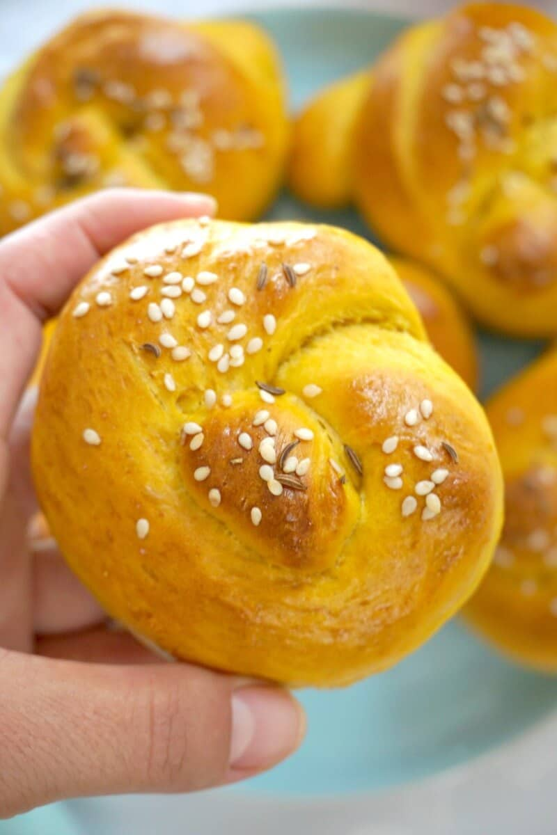 A pumpkin dinner roll with other rolls in the background