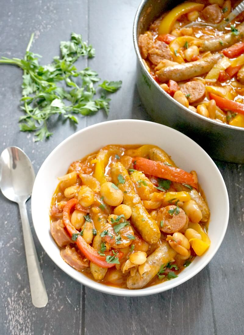 A white plate with sausage casserole and beans, a spoon next to it, some parsley leaves and a pot with more casserole