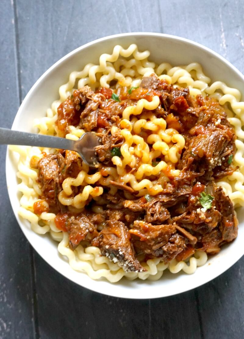 Overhead shoot of a white plate with pasta and shredded beef ragu