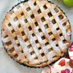 Overhead shoot of an apple pie with 2 green apples on the side