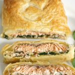 Salmon Wellington or Salmon en Croute, a gourmet dish with a festive touch. Salmon fillets on a bed of creamy spinach, dill, lemon and cream cheese sauce, wrapped in puff pastry, absolutely delicious and quick to make too.Take your dinner to the very next level, and impress your party guests this Christmas with this restaurant-style salmon recipe.