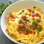 A white bowl with butternut squash spaghetti carbonara topped with cooked pancetta, parsley and parmesan.