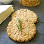 2 oatmeal cookies, one with a small rosemary sprig on top, and a wedge of brie