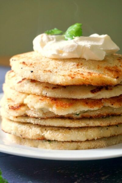 A pile of 7 potato pancakes topped with Greek yogurt and parsley leaves