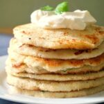 A pile of 7 mashed potato pancakes with yogurt and parsley leaves on top