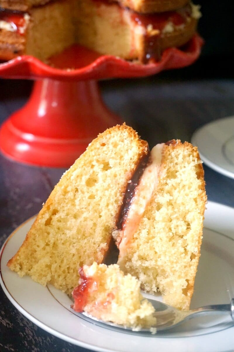 Close-up shoot of a slice of Victoria Sandwich Cake on a white plate