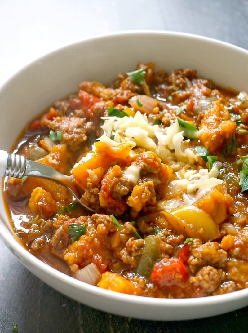 A white bowl with ground beef and sweet potato chili made in the crock pot