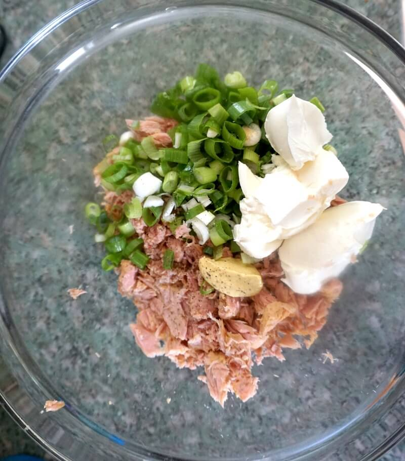 Overhead shoot of a glass bowl with flaked tuna, cream cheese and chopped onions to make a tuna dip