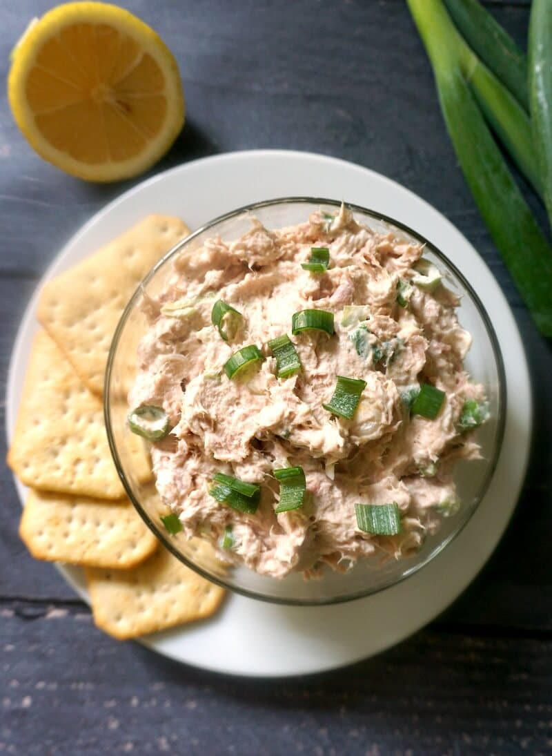 Overhead shoot of a glass bowl with tuna dip on a white plate with 4 crackers, half a lemon and spring onions on the side
