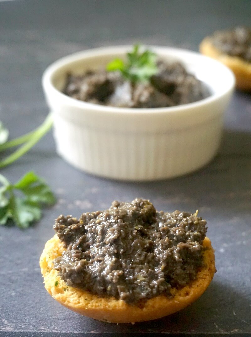 Black Olive Tapenade on a round crostini and a small white bowl of more tapenade in the background