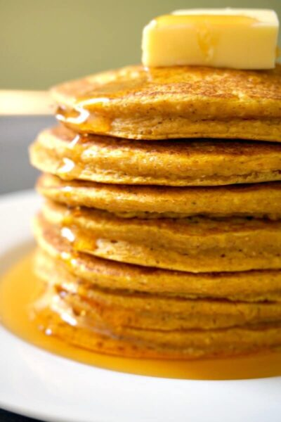 A stack of 7 oatmeal pumpkin pancakes topped with bit of butter and drizzled with maple syrup