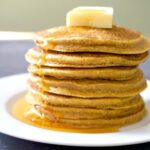 A stack of 7 oatmeal pumpkin pancakes with butter and maple syrup on top