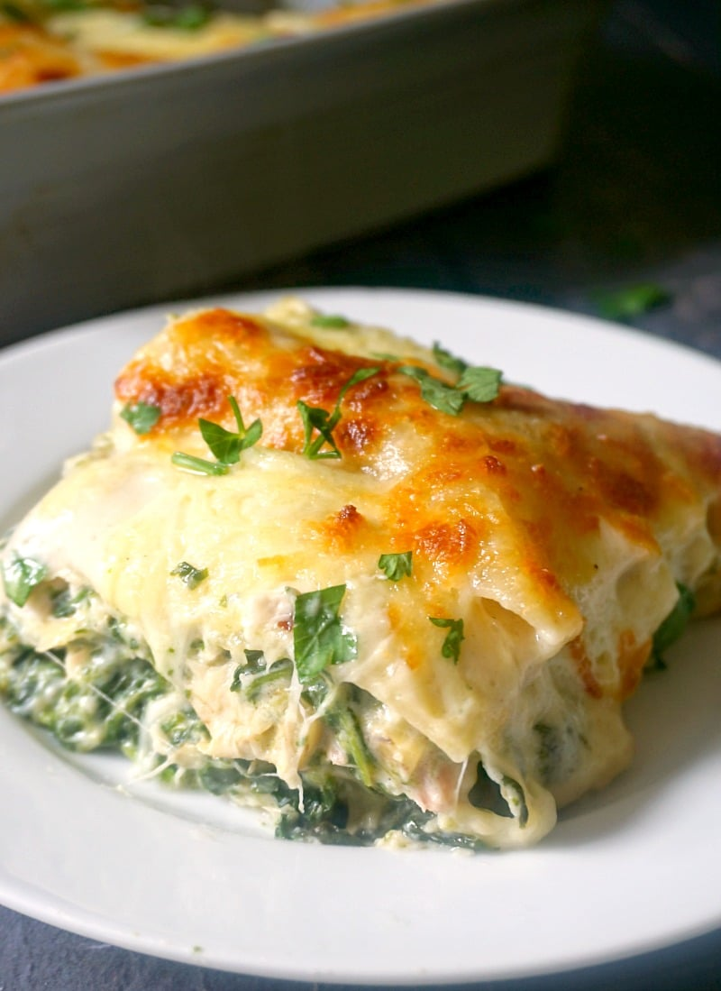 A white plate with a slice of leftover chicken, spinach and artichoke lasagna