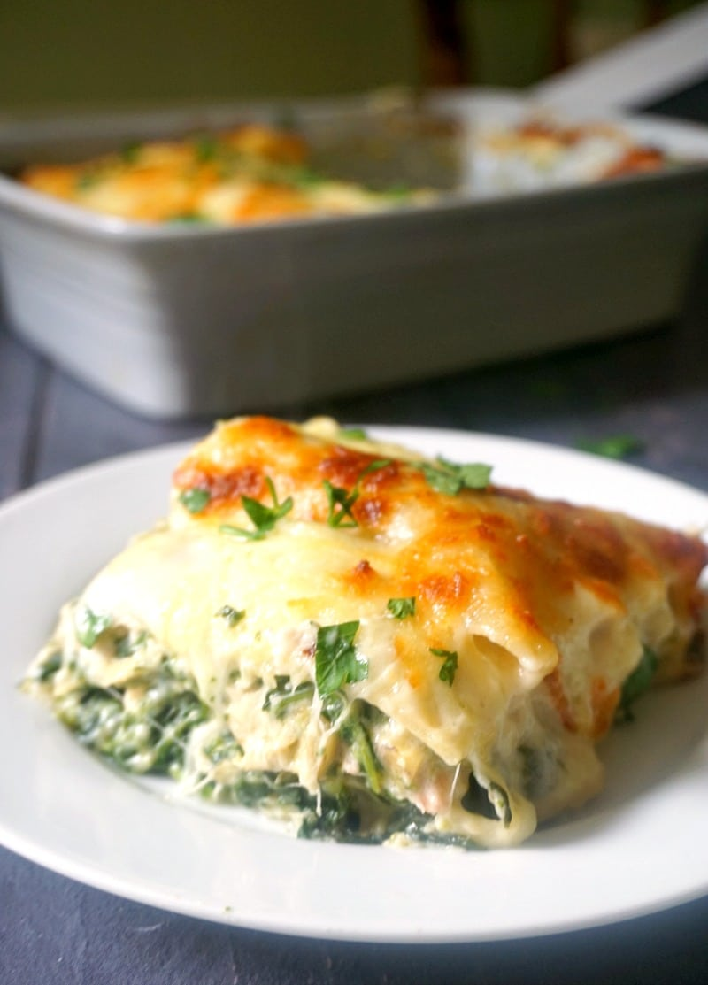 A slice of chicken lasagna with spinach and artichoke on a white plate with a dish of lasagna in the background