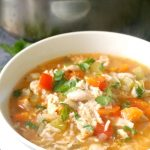 A white bowl of turkey rice soup with a pot in the background