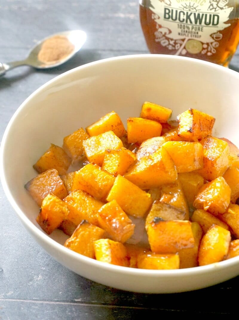 A white bowl with maple cinnamon roasted butternut squash cubes