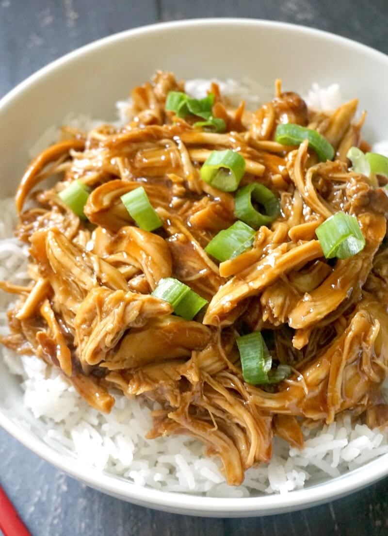 Close-up shoot of a white bowl with shredded chicken teriyaki over a bed of rice