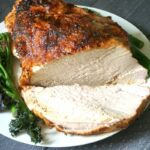 A roast turkey crown on a white plate with green veggies on the side