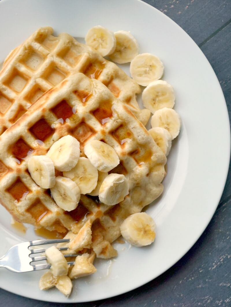 Overhead shoot of a white plate with 2 banana waffles topped with slices of banana and maple syrup