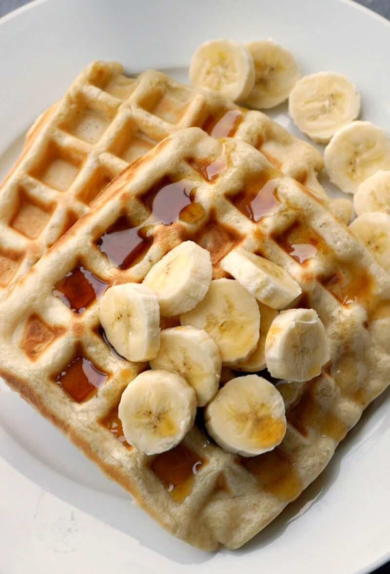 Close-up shoot of 2 waffles topped with slices of banana and drizzled with maple syrup