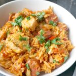 A white bowl of chicken and chorizo jambalaya garnished with fresh parsley