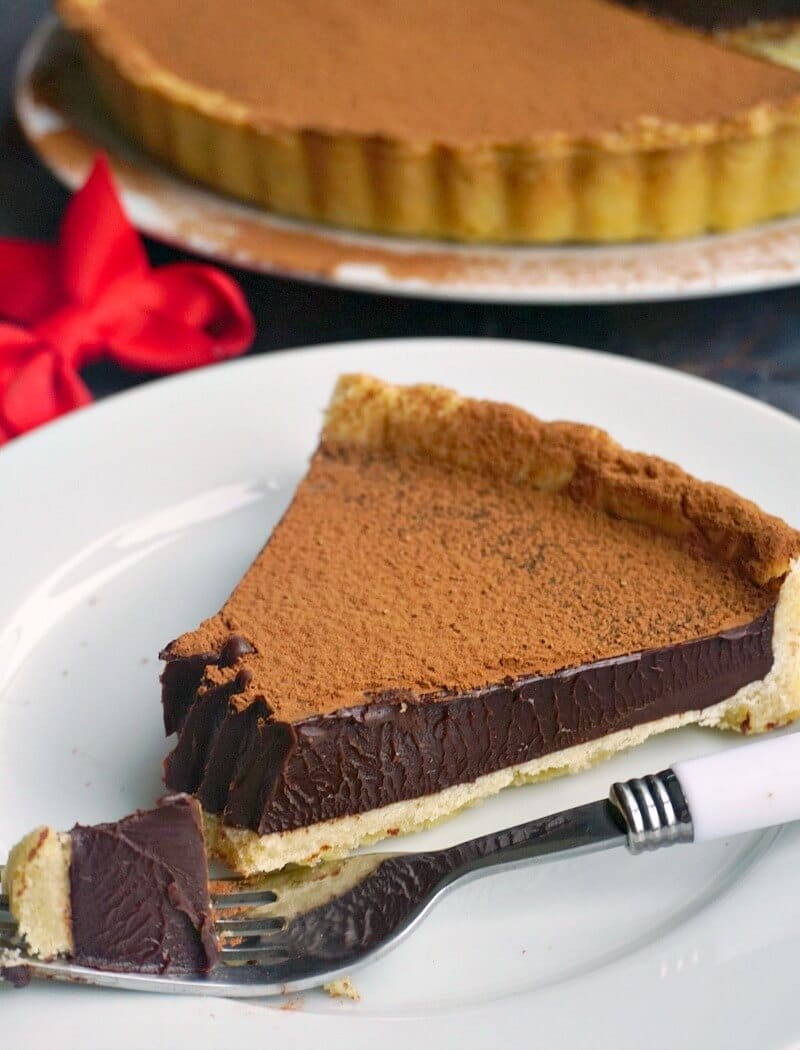 A slice of chocolate tart on a white plate with a fork next to it