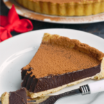 A slice of dark chocolate tart on a white plate with a fork next to it