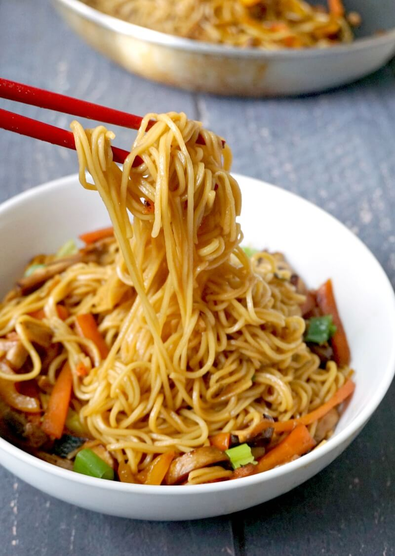 A white bowl with vegetable noodle stir fry and red chopsticks picking up some noodles off the bowl