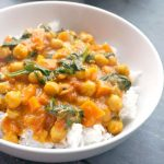 A white plate with coconut chickpea spinach curry on a bed of fluffy rice