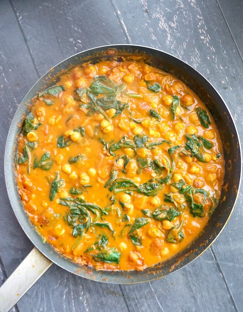 OVerhead shoot of a pan with coconut chickpea spinach curry