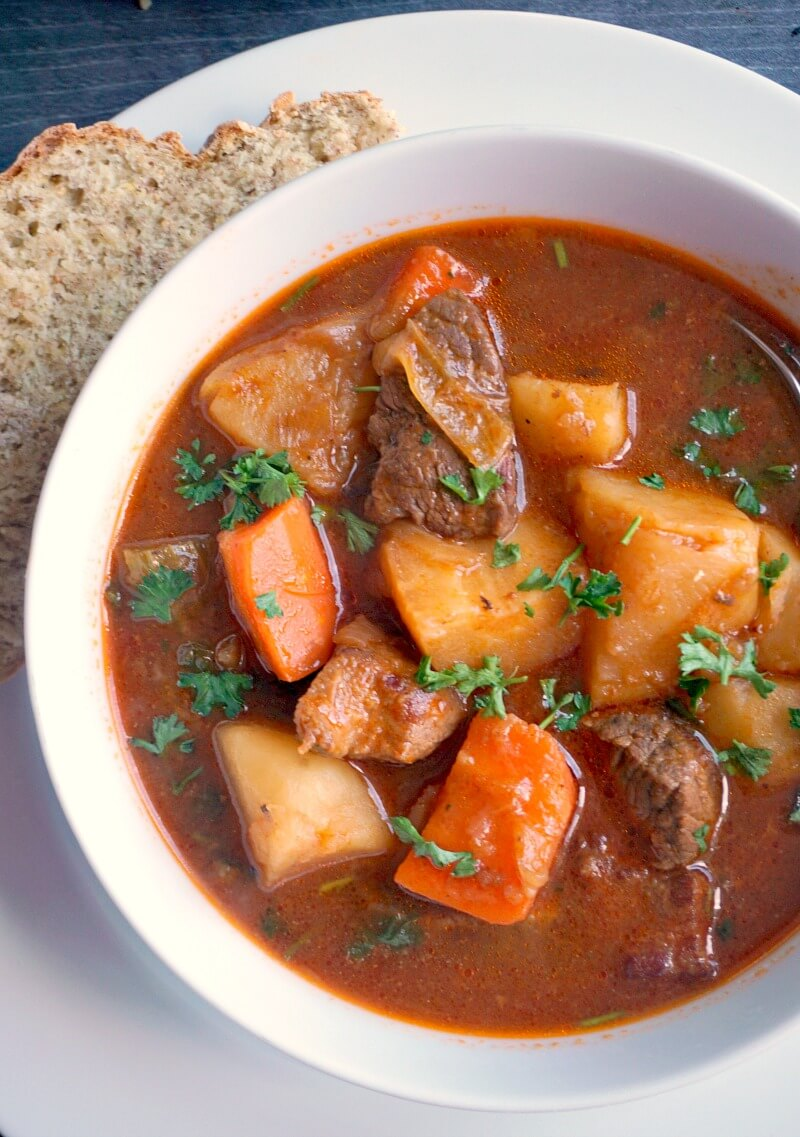 Overhead shoot of a white bowl with guinness beef stew and veggies