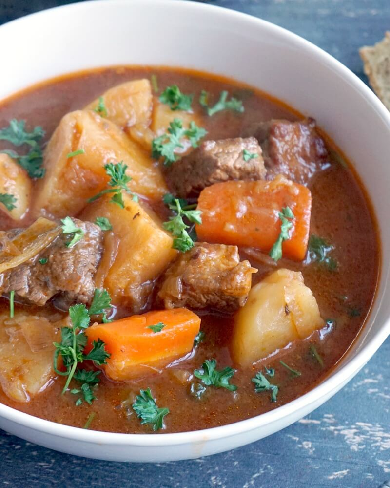 A white bowl with beef and vegetable stew