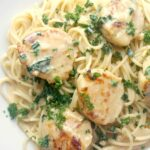Close-up shoot of a white plate with creamy spaghetti topped with scallops and chopped parsley