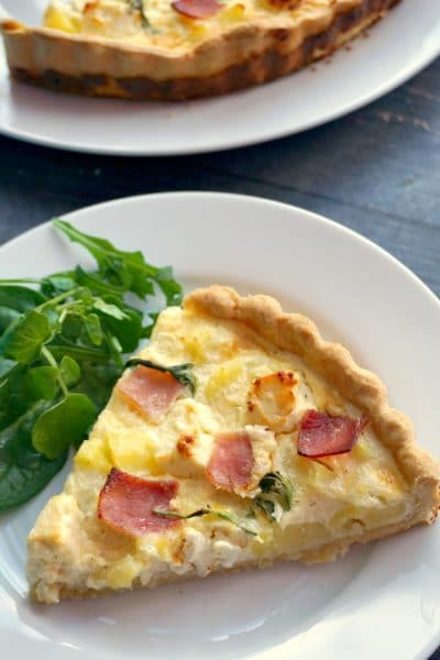 A white plate with a slice of potato and ham quiche and salad on the side