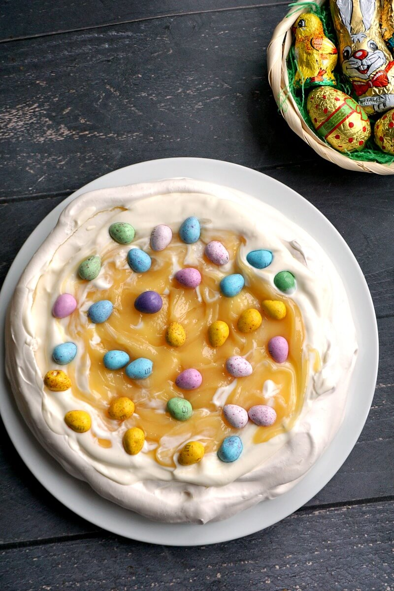 Overhead shoot of a pavlova on a white plate, topped with lemon curd and easter chocolate eggs