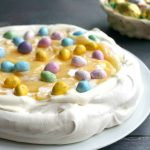 Lemon Curd Pavlova with Mini Chocolate Eggs, a delicious dessert for your Easter menu. It's crunchy and crisp on the outside, and soft, marshmallow-like inside, so light and delicate, perfect to impress your guests. The cream and lemon curd work wonderfully well together to give a silky, smooth texture, and the Easter eggs bring colour and a touch of Spring. It's an easy dessert that can be made to perfection at home, a real treat no matter the occasion. #pavlova, #easterdessert, #lemoncurd